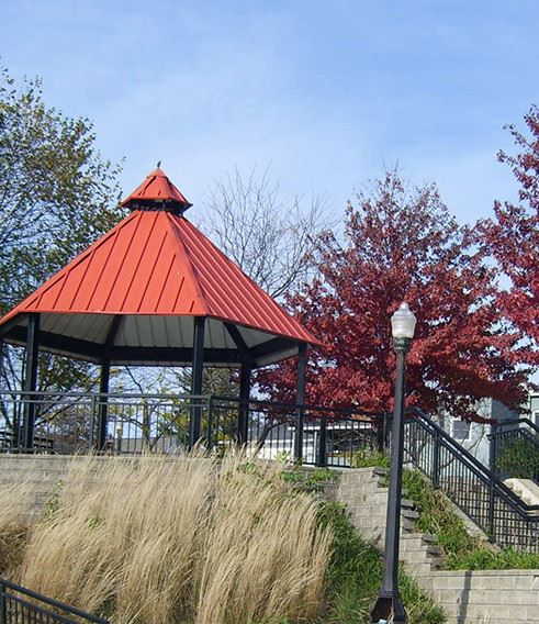 A gazebo with a red roof and stairs leading up to it